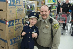 Lt. Tom Hodgson with the Utah County Sheriff's Office from the 2014 Shop With A Cop event. Tom is a member of the Shop With A Cop Committee and was one of the original officers that implemented the program 26 years ago.